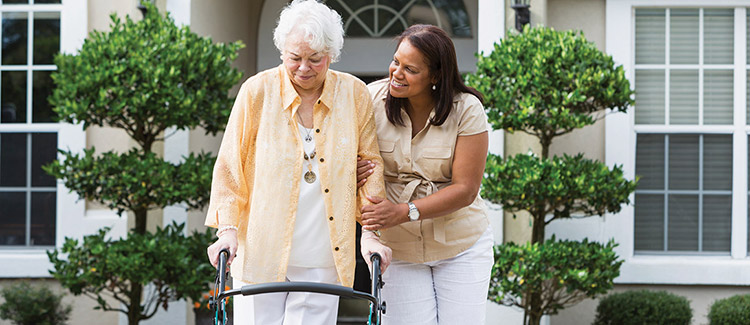 A caregiver is helping an old lady with the walker